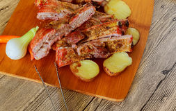 Delicious barbecued ribs seasoned with a spicy basting sauce and served with chopped fresh Stock Photos