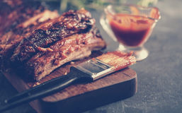 Delicious barbecued ribs seasoned with a spicy basting sauce. And served with chopped fresh vegetables on an old rustic wooden chopping board in a country royalty free stock photography