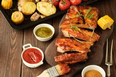 Delicious barbecued ribs seasoned with a spicy basting sauce and. Served with chopped fresh vegetables on an old rustic wooden chopping board royalty free stock photography
