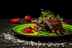 Delicious barbecued ribs seasoned with a spicy berry sauce and served with green seedlings on the plate, old rustic wooden stock images