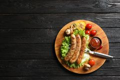 Delicious barbecued sausages served with vegetables and sauce on dark background. Space for text stock photography