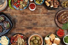 Outdoors Food Concept. Delicious barbecued steak, sausages and grilled vegetables on a wooden picnic table with copy space, top vi. Delicious barbecued steak Royalty Free Stock Images