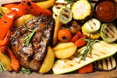 Delicious barbecued steak served with garnish and sauce. On wooden board, top view royalty free stock images