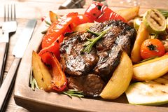 Delicious barbecued steak served with garnish on wooden board. Closeup stock image