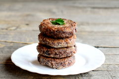 Delicious bean burgers on a plate isolated on old wooden background. Vegetarian burgers cooked of boiled red beans Royalty Free Stock Photo
