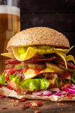 Delicious beef burger with nachos and beer on wooden table. Royalty Free Stock Photography