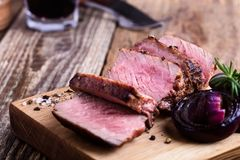 Delicious beef filet mignon. Served on wooden cutting board with roasted red onion and rosemary royalty free stock photos