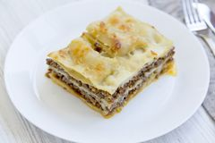 Delicious beef lasagne served on a white round plate, white wooden background. Side view royalty free stock photo