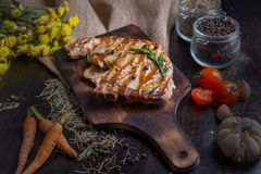 Delicious beef or pock steaks on wooden table. Grilled bbq steaks with fresh vegetable. With the ingredients organic for cooking. royalty free stock photos