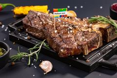 Delicious beef steak on black stone cutting board. Grilled meat served with grilled corn, garlic, rosemary, sauces, chilli and royalty free stock images