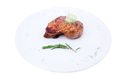 Delicious beef steak with herb butter. Delicious beef steak with herb butter and rosemary bunch. Isolated on a white background Royalty Free Stock Photo