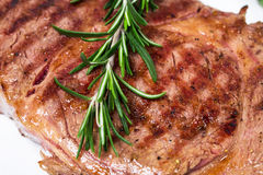 Delicious beef steak with rosemary bunch. Royalty Free Stock Images
