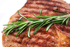 Delicious beef steak with rosemary bunch. Stock Photo