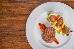 Delicious beef steak with sauce and vegetable, served on white plate, modern gastronomy, michelin restaurant.  stock photography