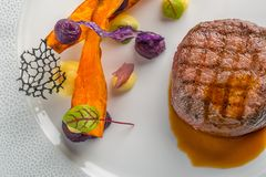 Delicious beef steak with sauce and vegetable, served on white plate, modern gastronomy, michelin restaurant.  royalty free stock photography