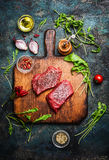 Delicious beef steak on vintage cutting board with fresh various ingredients for tasty cooking on rustic wooden background royalty free stock photos