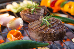 Delicious beef steaks with vegetable on a barbecue grill. royalty free stock photos