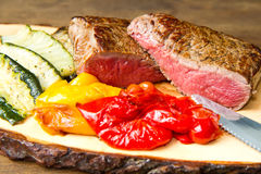 Delicious beef steaks on white dish with grilled vegetables Stock Photography
