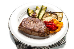 Delicious beef steaks on white dish with grilled vegetables Royalty Free Stock Photo