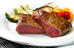 Delicious beef steaks on white dish with grilled vegetables Stock Image