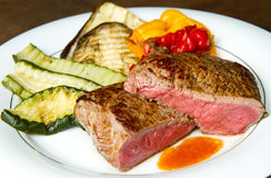 Delicious beef steaks on white dish with grilled vegetables Stock Photos