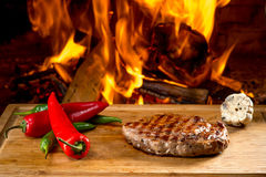 Delicious beef steaks on wooden desk and fire Stock Photos