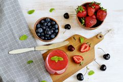 Delicious berries smoothie, strawberry, blueberry, cherry. Wooden background, summer drink concept royalty free stock photos