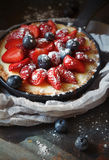 Delicious berry tart with cream on dark background. Delicious berry tart tartlet with cream on dark background Stock Images