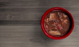 Delicious bihuny soup in a red bowl on a bamboo board. Royalty Free Stock Images