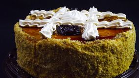 Delicious birthday cake with nuts and prunes. Delicious birthday cake with nuts and prunes on black background stock photo