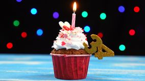 Delicious birthday cupcake with burning candle and number 34 on multicolored blurred lights background