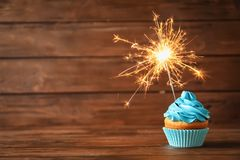 Delicious birthday cupcake with sparkler. On table Royalty Free Stock Photo