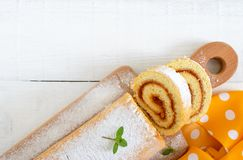 Delicious biscuit roll with apricot jam and powdered sugar on a white wooden table. Dessert for breakfast. Top view. Copy space royalty free stock photography