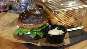 Delicious black bread burger With Round French Fries stock footage
