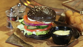 Delicious black bread burger With Round French Fries stock video footage