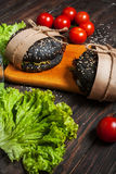 Delicious black burgers in craft paper on cutting board. dark wood table Stock Image