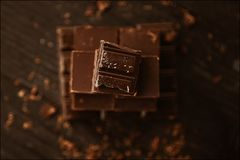 Delicious black and milk chocolate on a brown background Royalty Free Stock Image