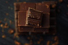 Delicious black and milk chocolate on a brown background Royalty Free Stock Photography