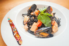 Delicious black spaghetti Neri with cream sauce and seafood Stock Photos