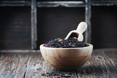 Delicious black tea with petals on the wooden table Stock Photos