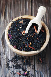 Delicious black tea with petals on the wooden table Stock Images