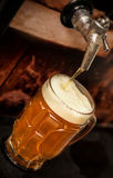 Delicious blonde craft beer filled into a pint glass on wooden table.  royalty free stock photos