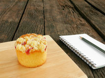 The delicious blueberry muffin and small note book with pencil Stock Photos