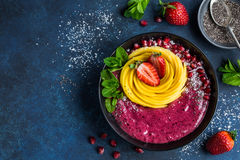 Delicious blueberry smoothie bowl with mango and strawberry royalty free stock image