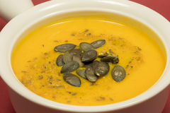 Delicious bowl of autumn pumpkin soup. Delicious bowl of homemade autumn pumpkin soup garnished with spices and dried pumpkin seeds stock photos