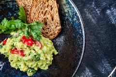 Delicious bowl of Guacamole with bread close up on dark table with copy space. green, naturally made traditional guacamole. stock photos