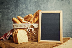 Delicious bread and rolls in wicker basket Stock Images