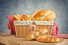 Delicious bread and rolls in wicker basket Stock Photos