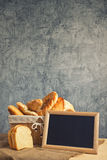 Delicious bread and rolls in wicker basket Stock Image