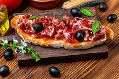 Delicious bread toast with natural tomato, extra virgin olive oil, Iberian ham, black olives and basil leaves. On wooden background stock photos